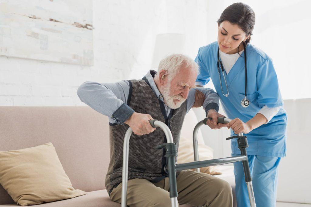 Foto de um senhor e uma enfermeira auxilio-cuidador