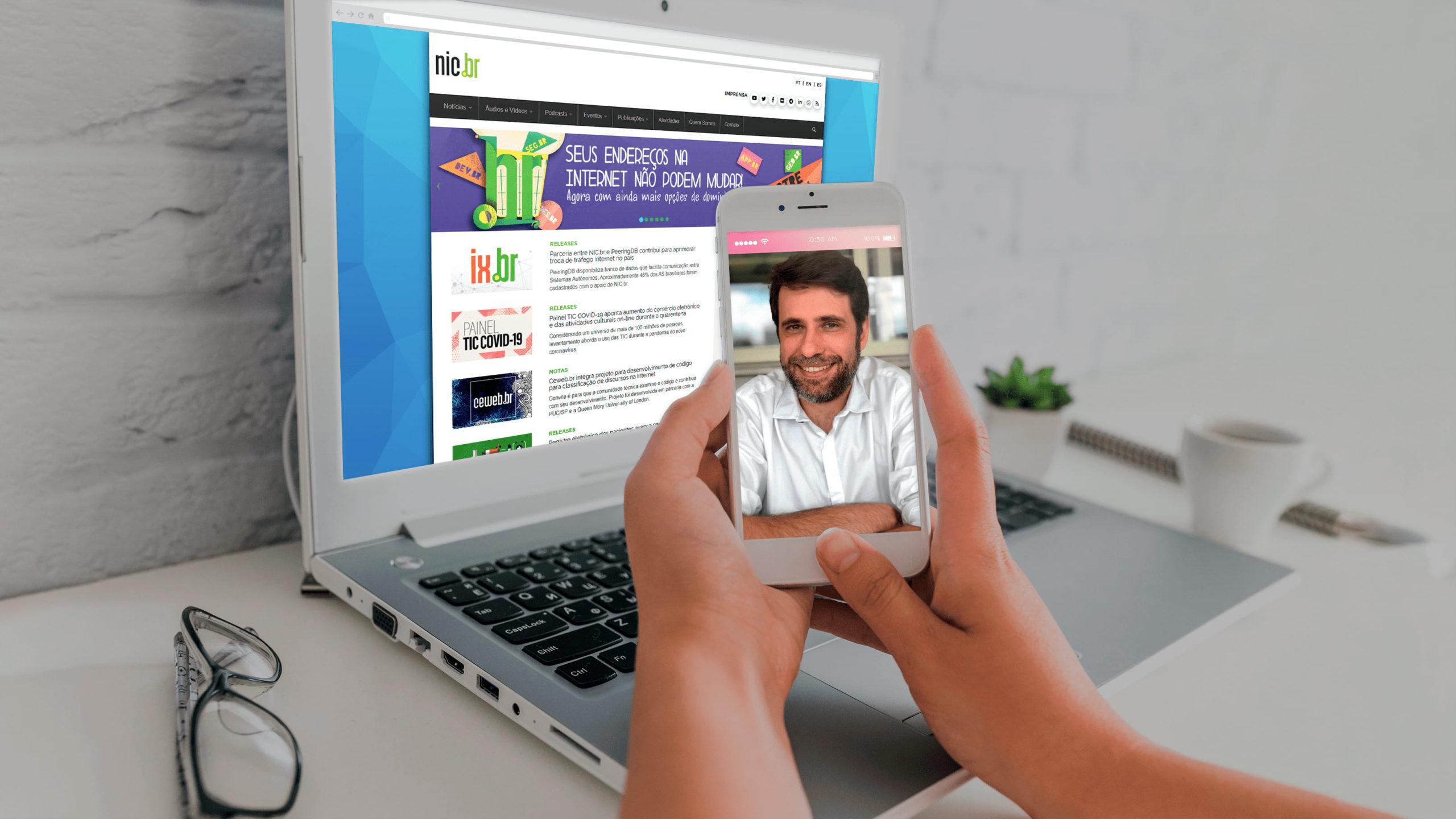 Acessibilidade na Web, com Reinaldo Ferraz em um celular, e o NIC.br na tela do notebook