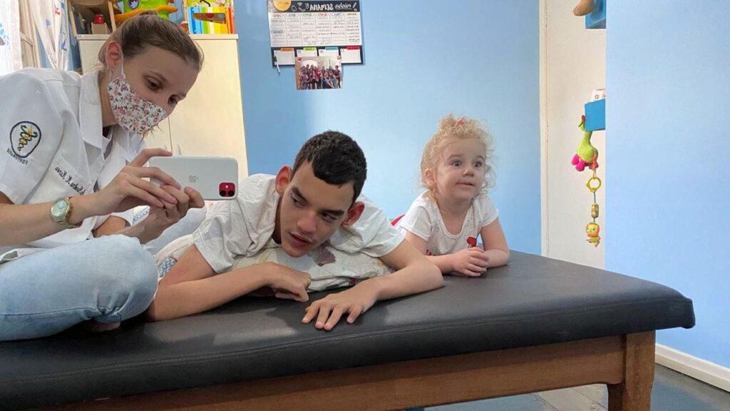 Fisioterapeuta Carol, fotografando paciente com paralisia cerebral e sua irmã