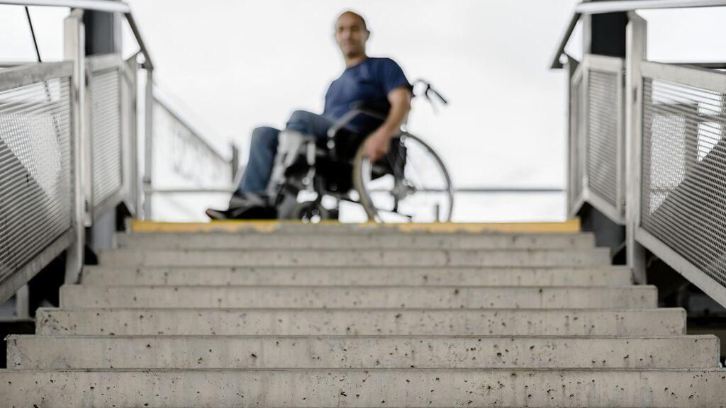 """Fotografia com um cadeirante parado em frente uma escada para o texto """"Arquiteto Especialista em Acessibilidade"""""""