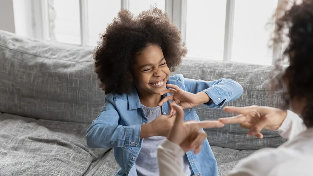 Fotografia de uma criança negra usando Libras para se comunicar - Setembro Azul 2020