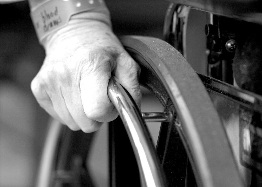 Mão tocando cadeira de rodas