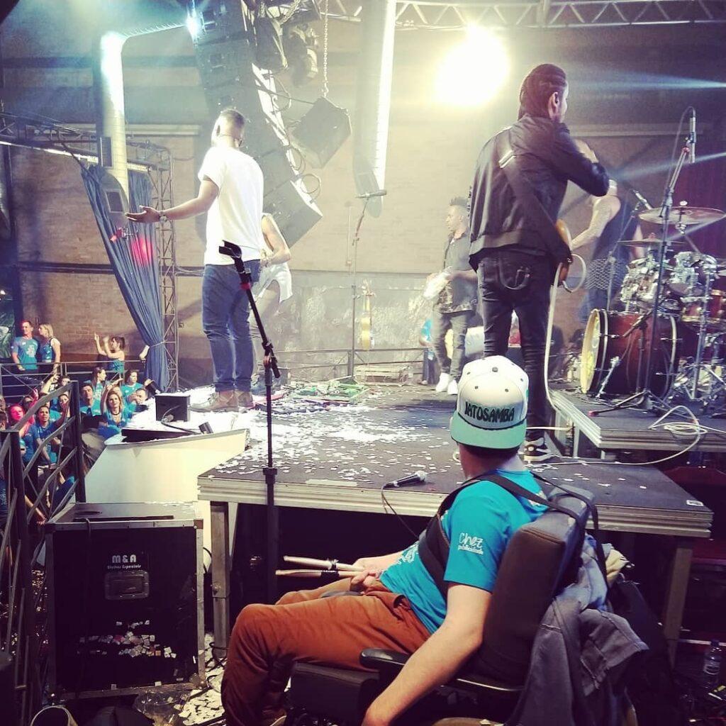Murilo está na cadeira de rodas, ao lado de um palco com músicos. Ele está de lado, e se rosto não se vê. Artigo Bóra sair?