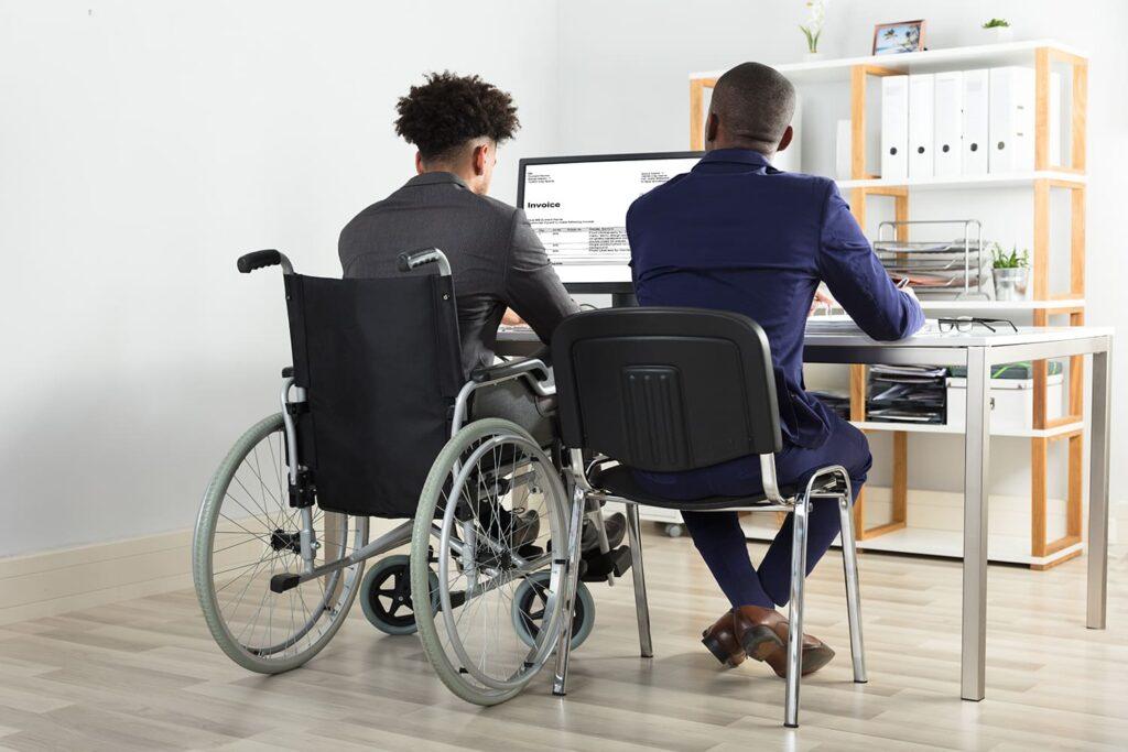 Dois homens de negócios, sendo um cadeirante para o texto Capacitismo e Trabalho em 2020: Pesquisa revela números preocupantes