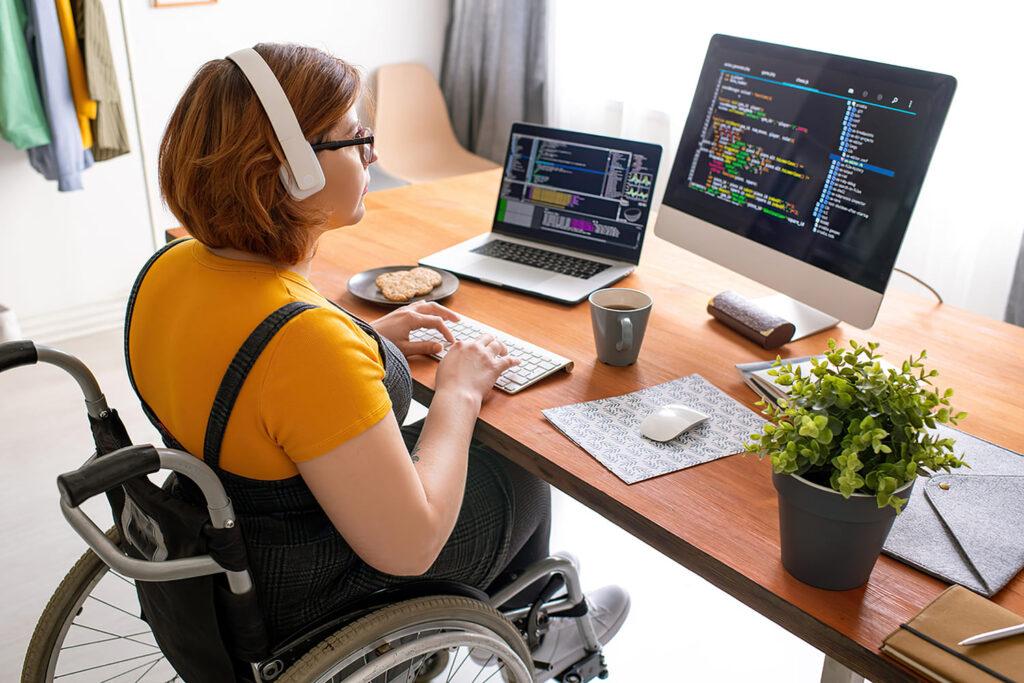Mulher cadeirante digita no computador ilustrando texto sobre a live Inclusão Digital no Contexto da Pandemia