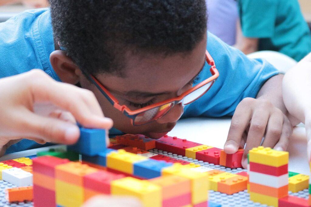 Foto de criança negra com deficiência visual ilustrando LEGO Braille Bricks: Novidade às vésperas do Dia Mundial do Braile