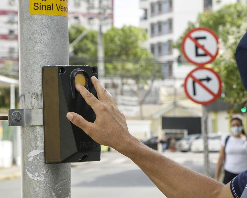 Homem acionando botão do equipamento para artigo Semáforos sonoros são instalados em Recife