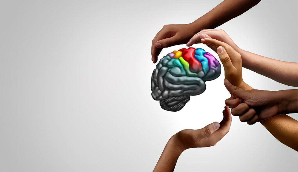 Mãos em volta de um cérebro ilustra Dia Internacional da Síndrome de Asperger