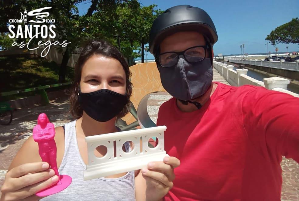 Duas pessoas, replica de mureta dos canais da cidade, ilustra Santos às Cegas, passeio para pessoas com deficiência visual
