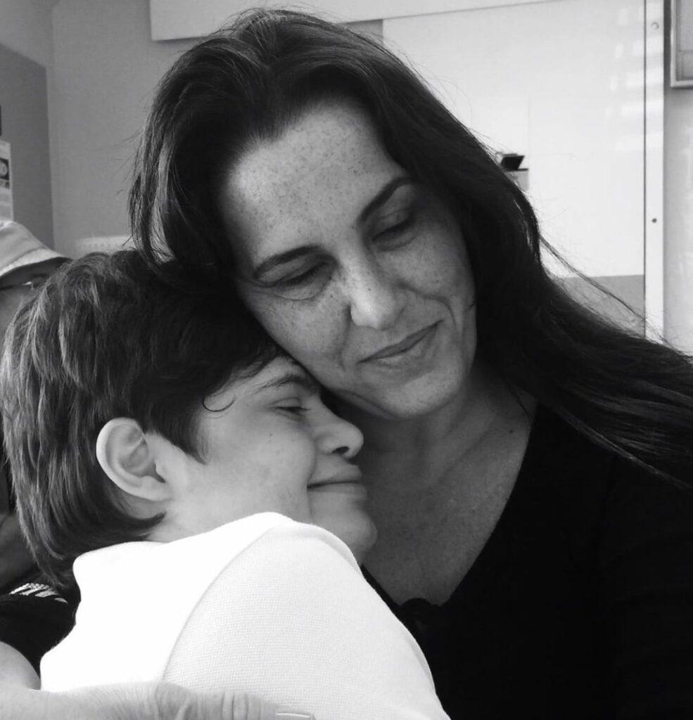 """Foto da mãe Daniela abraçada ao filho Augusto, que tem síndrome de down, ilustrando o artigo """"Conscientização e luta contra o capacitismo estrutural"""""""