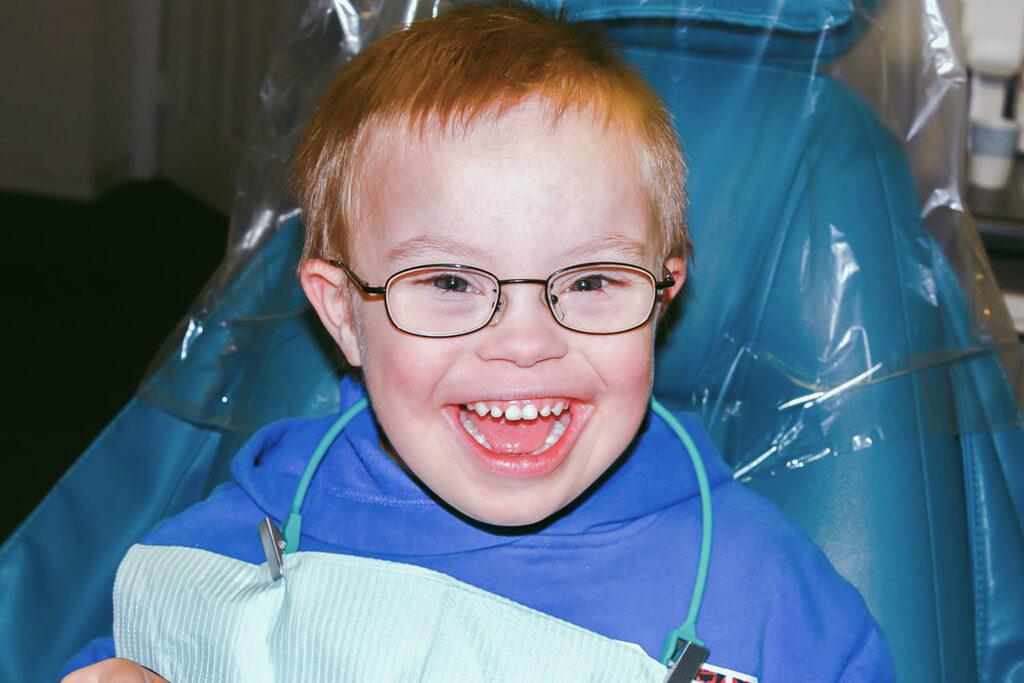 Criança com síndrome de down sorrindo, para 4 dicas para a saúde bucal na trissomia 21.