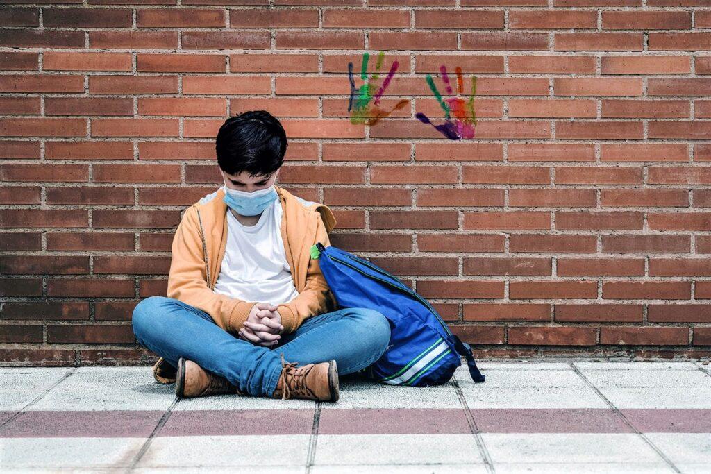 Jovem sentado no chão, descrito na legenda, especial Famílias de autistas na pandemia em 2021.