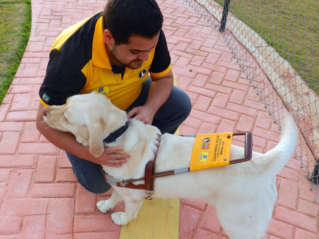 Foto de Murilo e seu cão-guia, descritos na legenda do Dia Internacional do Cão-Guia 2021.