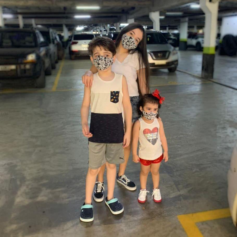Três irmãos no estacionamento do condomínio, com descrição na legenda de Famílias de autistas na pandemia em 2021.