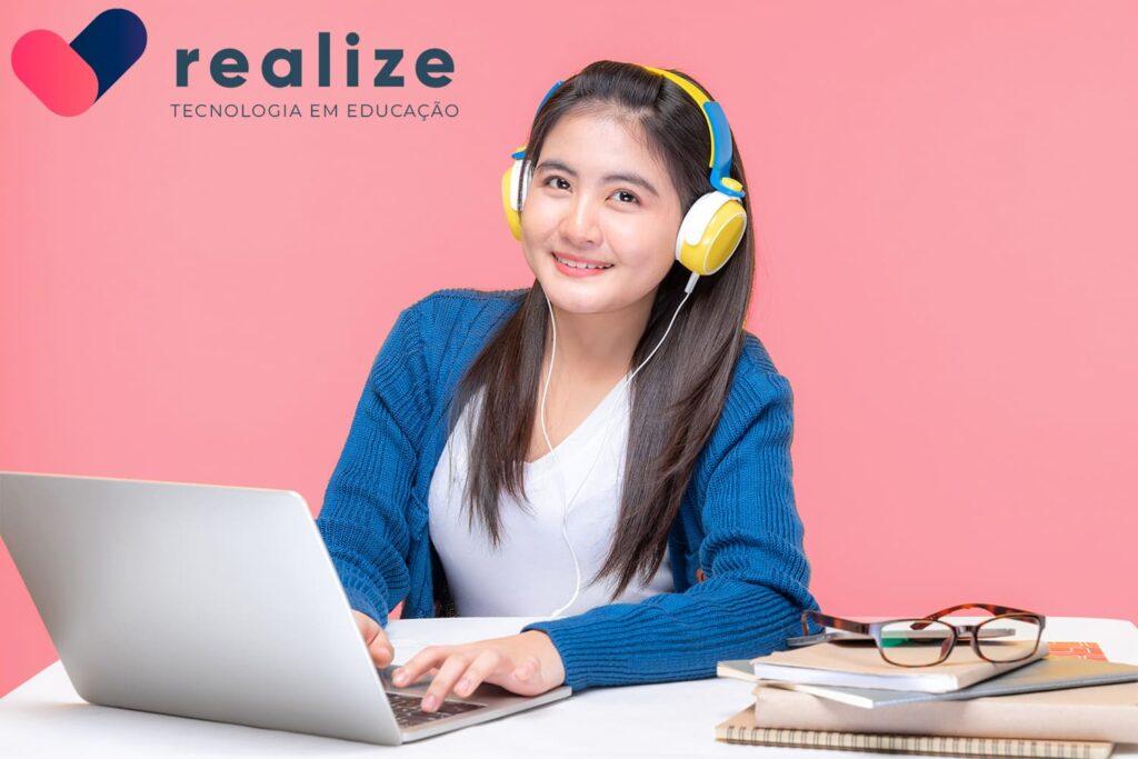 Mulher estudando com fone e notecook, descrita na legenda, realize, tecnologia em educação.
