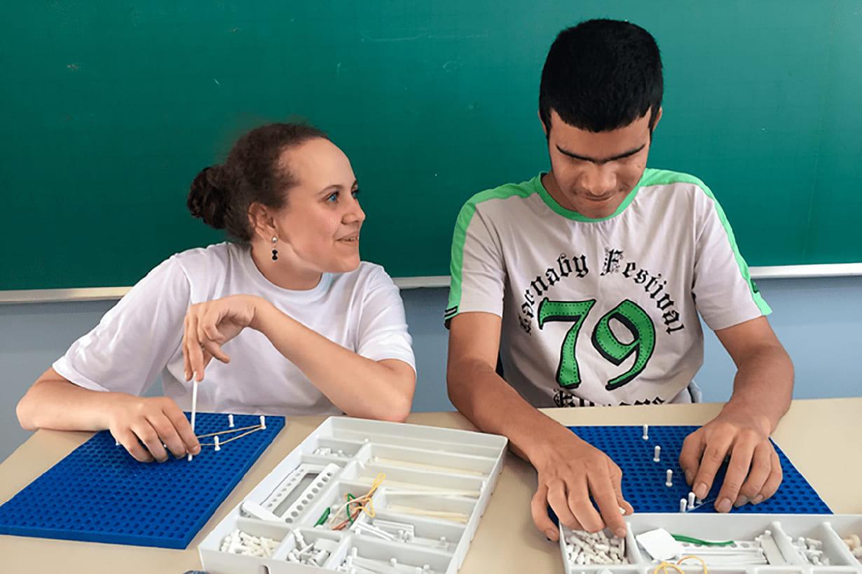Duas pessoas utilizando o Multiplano, ferramenta pedagógica de matemática para cegos, em sala de aula. À esquerda, mulher branca com cabelos presos em coque está olhando para o lado. À direita, jovem rapaz de pele parda e cabelos pretos está manuseando a ferramenta pedagógica em cima de uma mesa. Atrás deles, uma lousa de sala de aula.