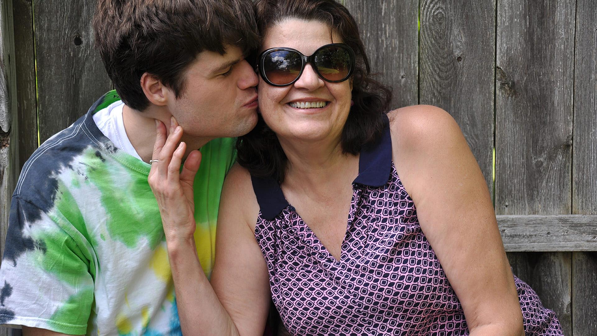 """Filho beijando o rosto da mãe. Descrição na legenda da reportagem sobre """"Os desafios do autista adulto""""."""