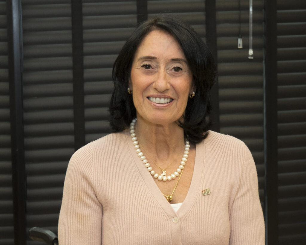 Fotografia da Secretária de Estado dos Direitos da Pessoa com Deficiência Célia Leão. Mulher branca de cabelos pretos, na altura dos ombros. Está sorrindo, usa cadeira de rodas, suéter rosa, colar e brincos.