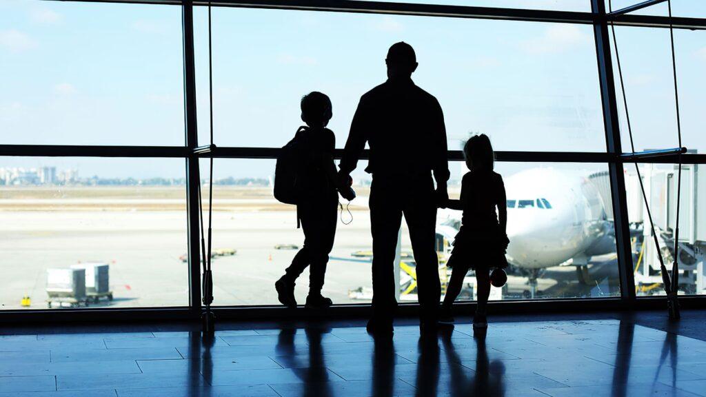 Pai, filho e filha no aeroporto, olhando para a pista de pouso. Descrição na legenda.