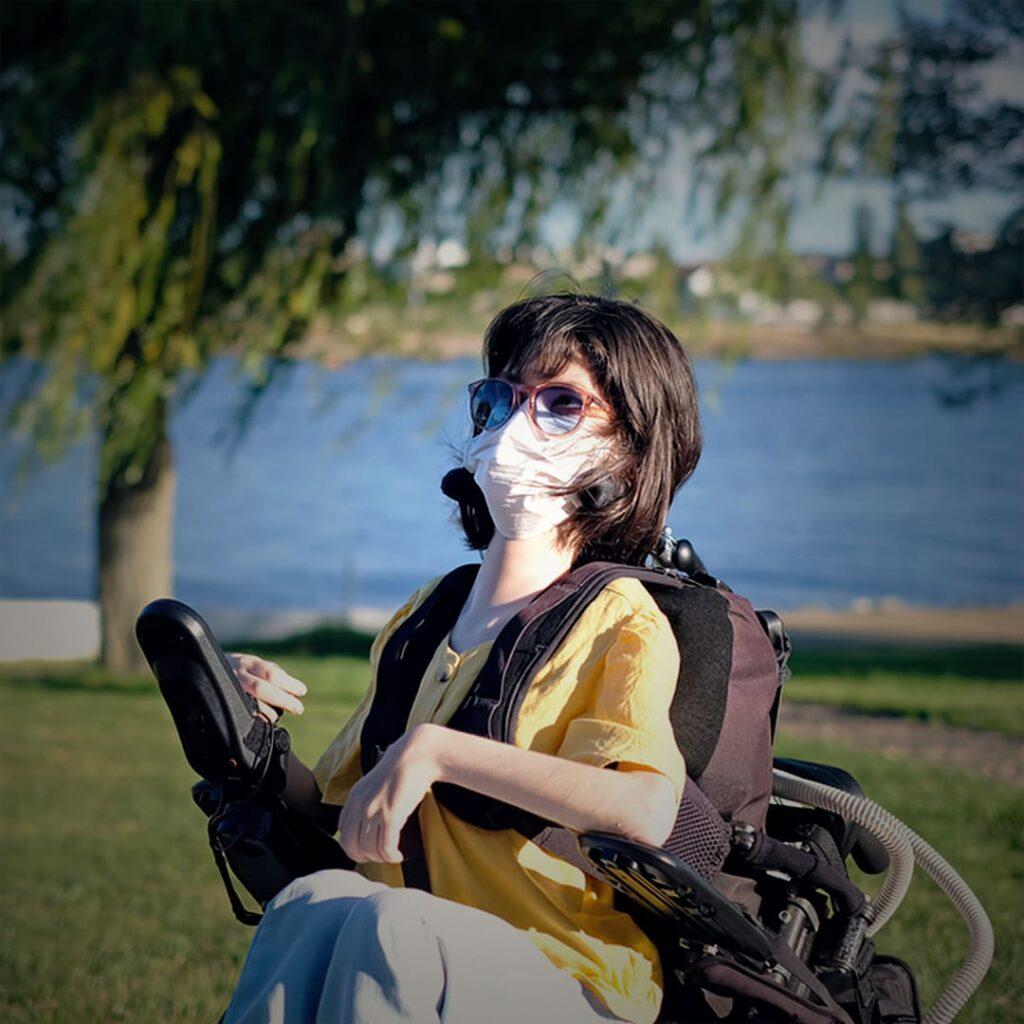 Pessoa com Síndrome de Duchenne, em cadeira de rodas, com descrição na legenda.