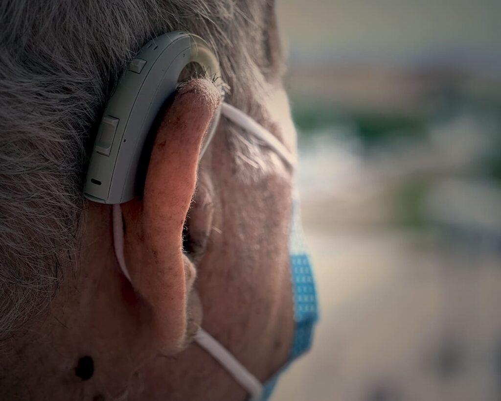 """Pessoa de cabelos grisalhos, com aparelho auditivo, ilustrando texto sobre """"Como lidar com o idoso com perda auditiva""""."""