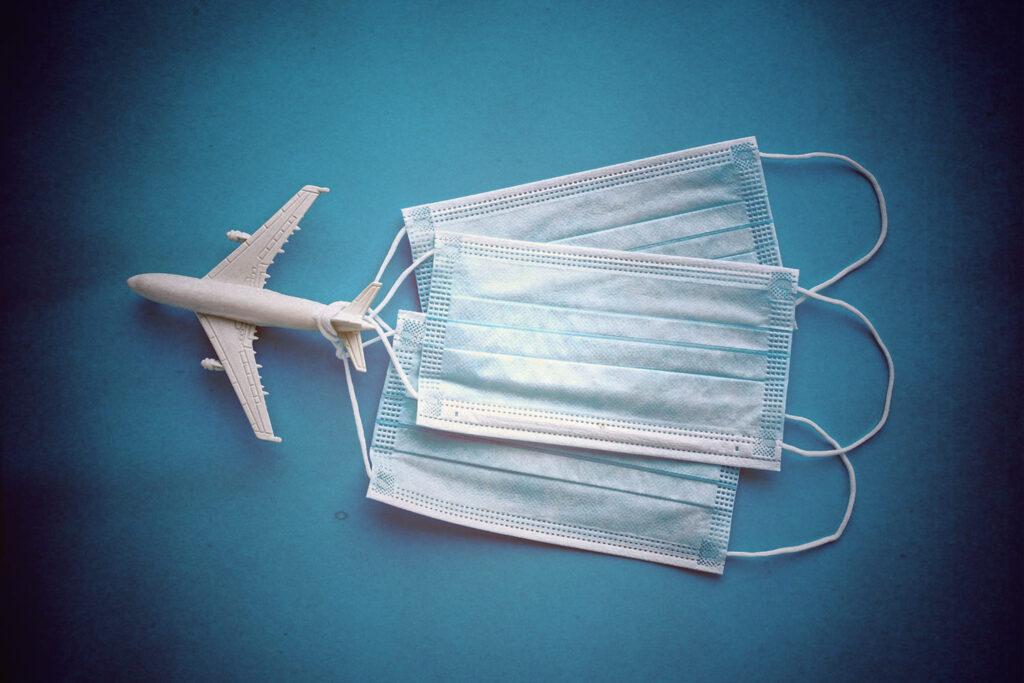 Fotografia em fundo azul e cantos escurecidos, de um aviãozinho branco, de brinquedo, com três máscaras hospitalares amarradas à causa da aeronave.