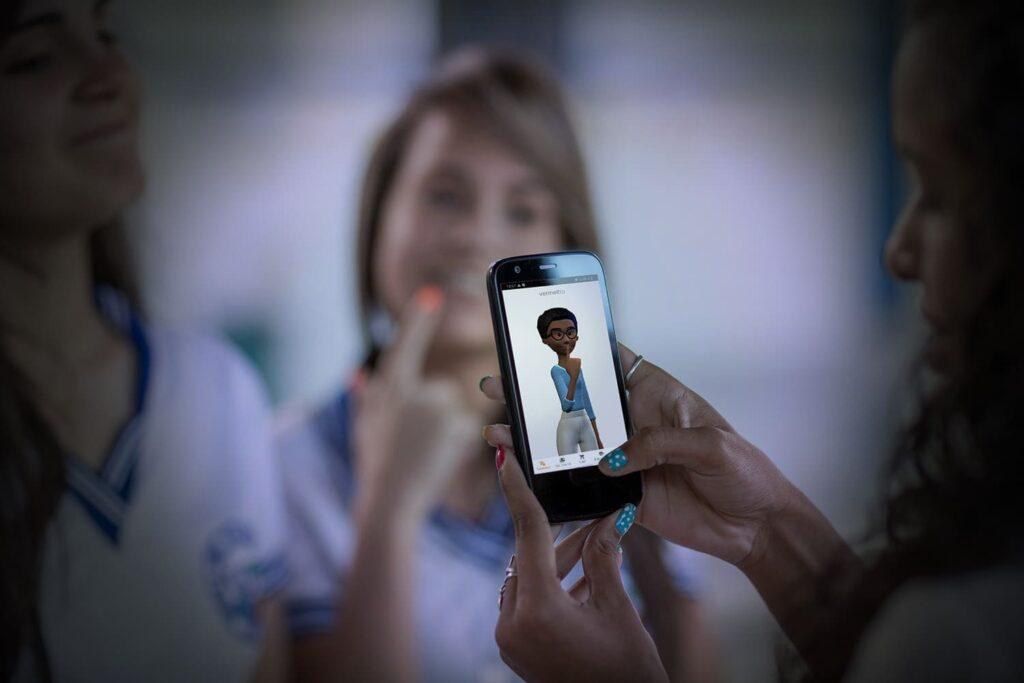 Foto com três garotas e um celular com a tradutora virtual de Libras, Maya, da Hand Talk.