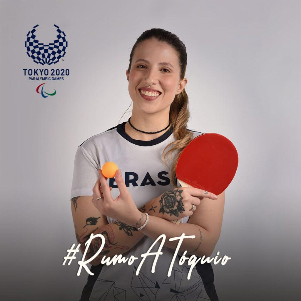 Foto da mesa-tenista segurando raquete e bolinha de tênis de mesa.
