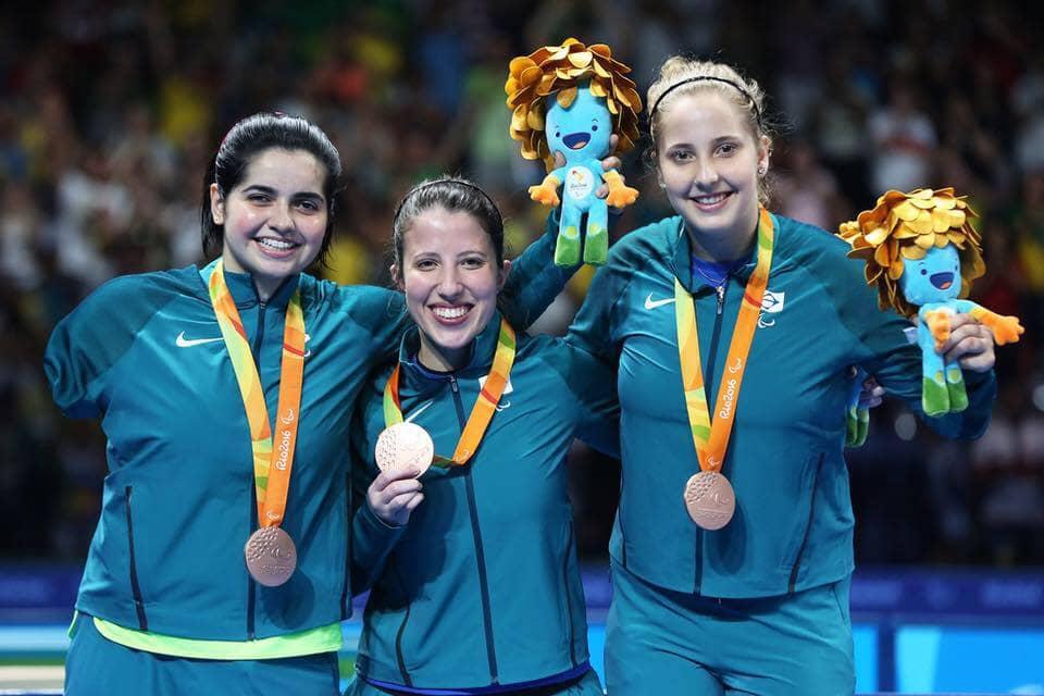 Fotografia das Paralimpiadas Rio 2016, no momento de entrega da medalha de bronze às paratletas brasileiras do tênis de mesa, com descrição na legenda.