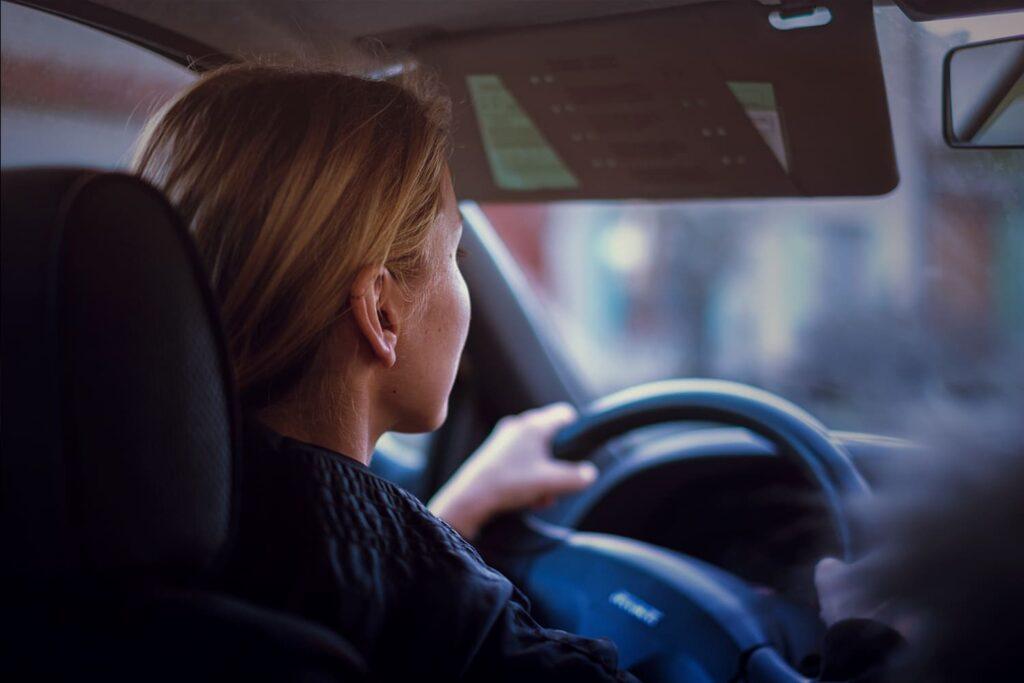 Fotografia no interior de automóvel, com motorista segurando o volante.