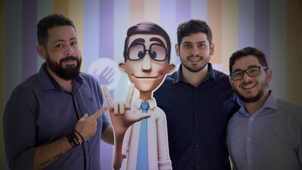 Foto dos fundadores da Hand Talk, junto do avatar Hugo, com detalhes na legenda.
