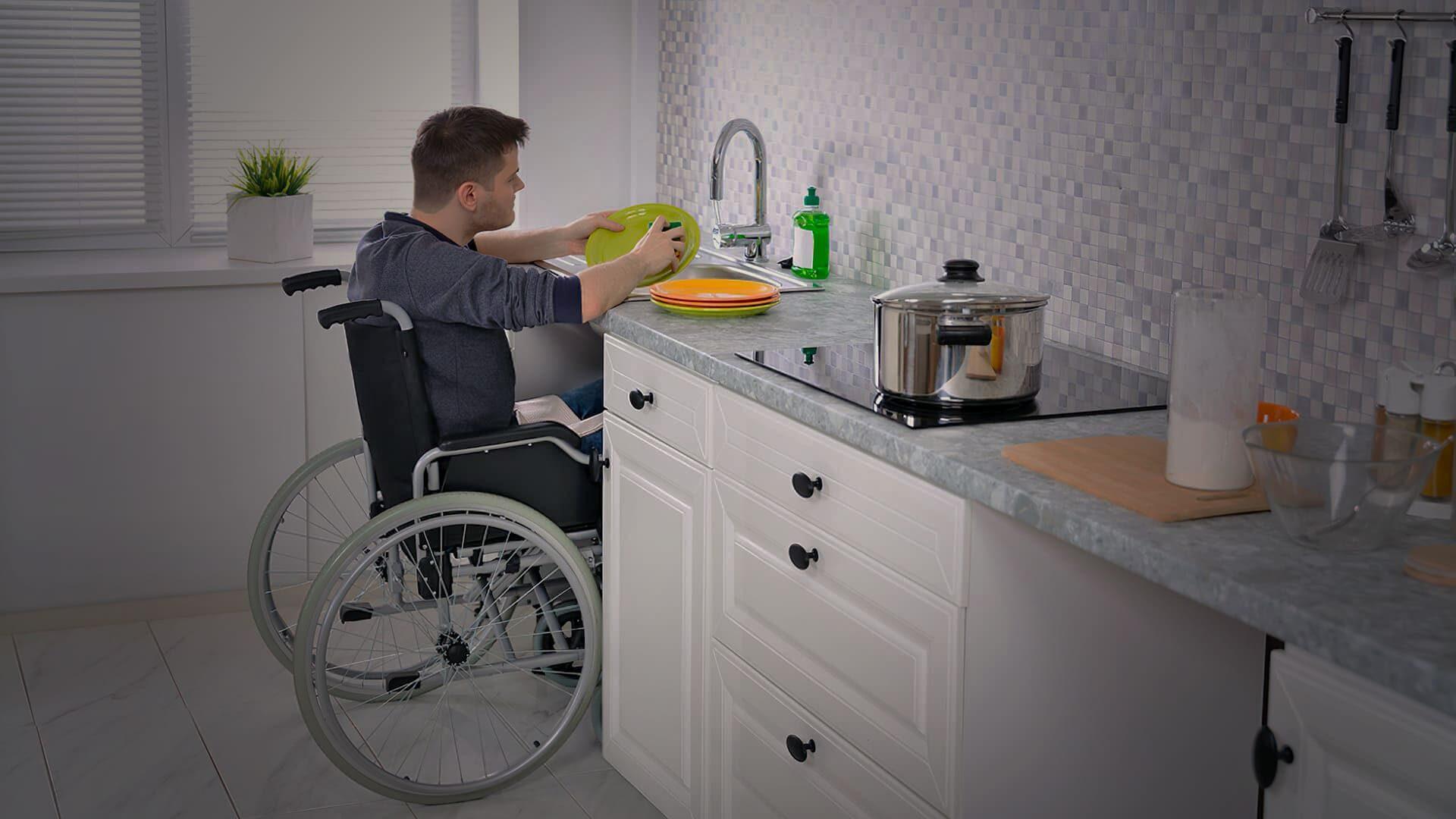 Homem em cadeira de rodas lavando a louça. Descrição na legenda do artigo sobre a importância da acessibilidade em projetos arquitetônicos.