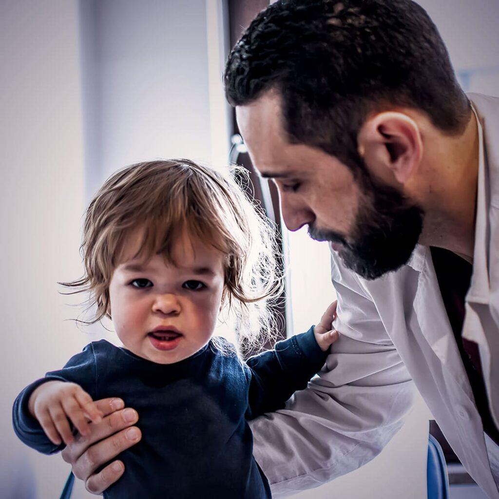 Criança com nanismo e médico, descritos na legenda.