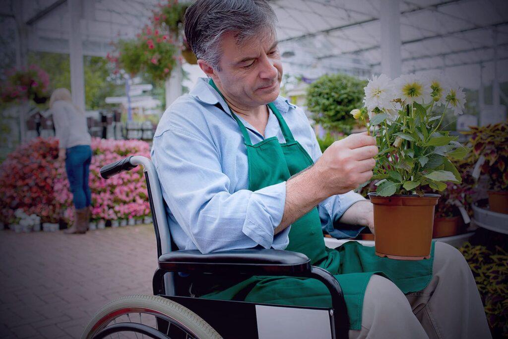 Cadeirante trabalhando em floricultura, com descrição detalhada na legenda da foto.