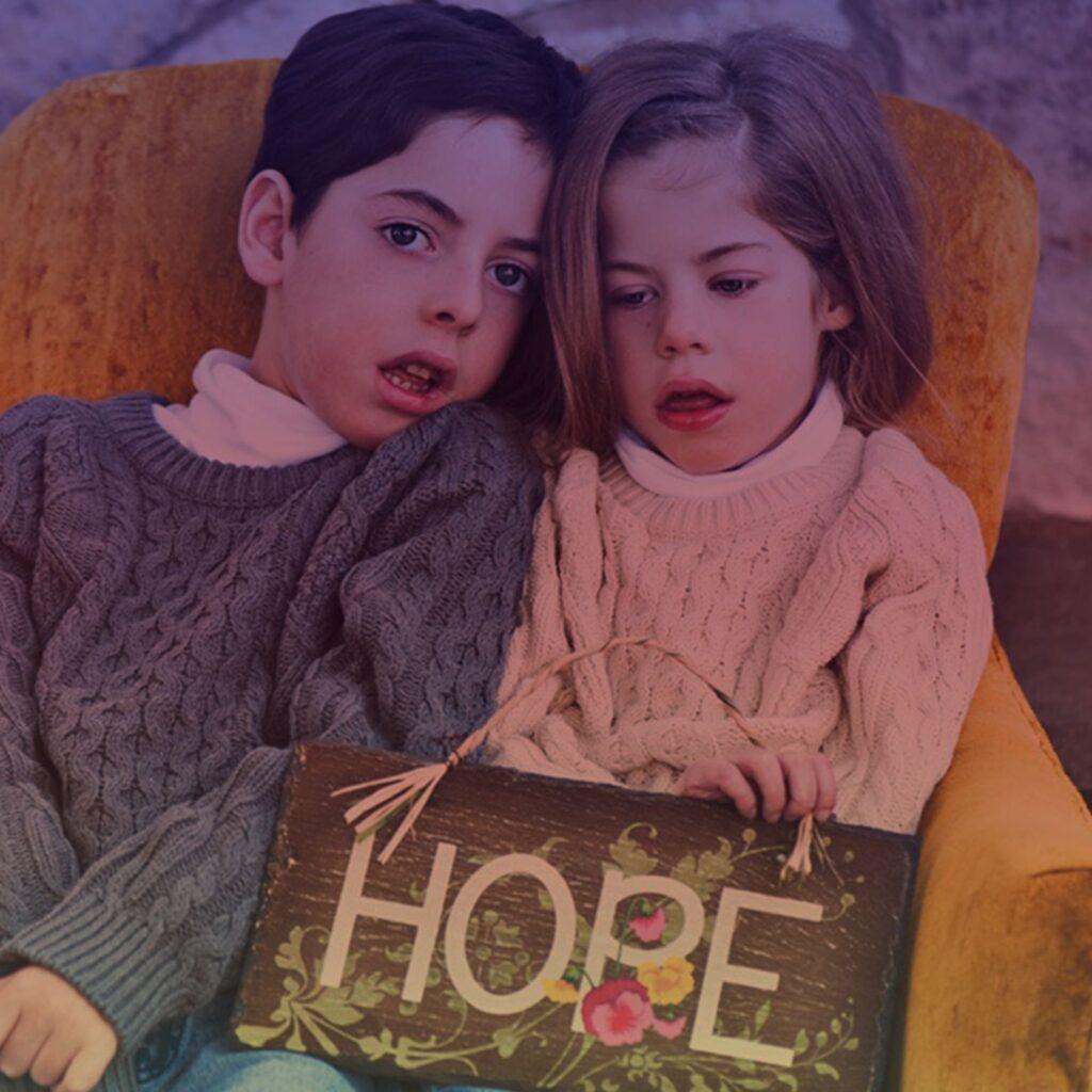 Foto dos irmãos Noah e Laine, crianças com doença de Batten, com placa escrito esperança em inglês.