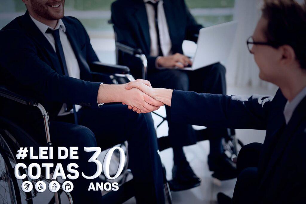 Homens de negócios em cadeira de rodas, com logo do evento de 30 anos da Lei de Cota.