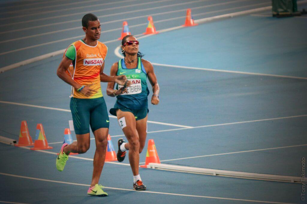 Foto de paratleta correndo com seu atleta-guia, descritos na legenda.