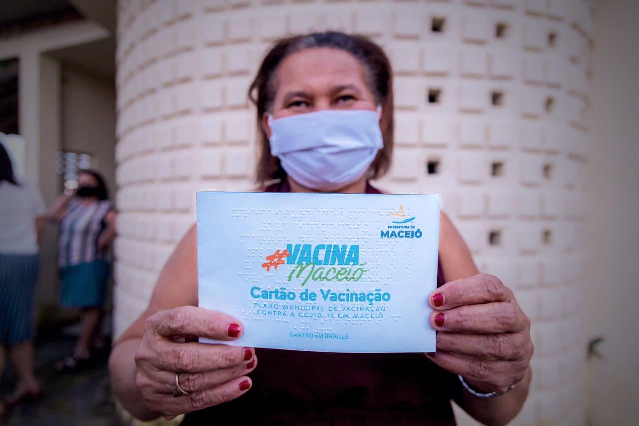 Fotografia da presidente da Associação de Cegos de Alagoas, Cícera Oliveira da Cruz segurando o cartão de vacinação da COVID-19 em braille.