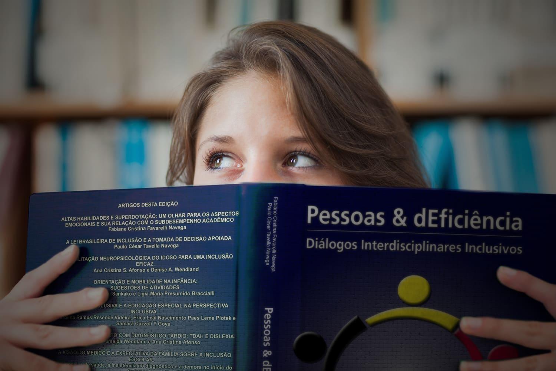 Pessoa lendo o livro, ilustrando o lançamento do livro Pessoas e dEficiência: Diálogos Interdisciplinares Inclusivos.