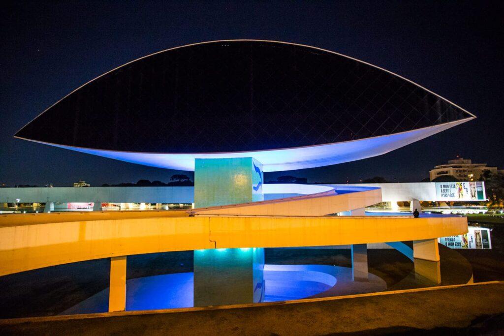 Foto mostrando iluminação do Museu Oscar Niemeyer, para Ação do Dia Mundial da Síndrome do X Frágil (SXF).