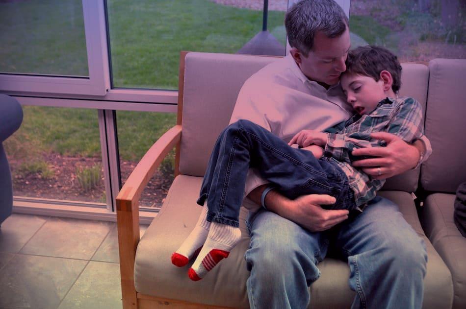 Foto de pai e filho, criança com doença de Batten, e descrição na legenda.
