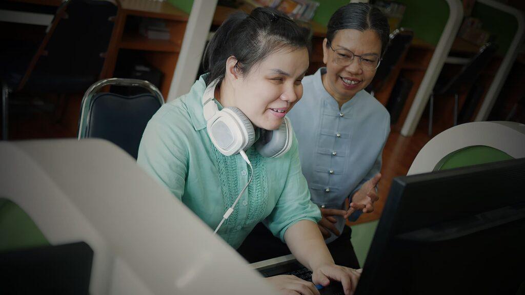 Mulher com deficiência visual utilizando computador na companhia de outra mulher.