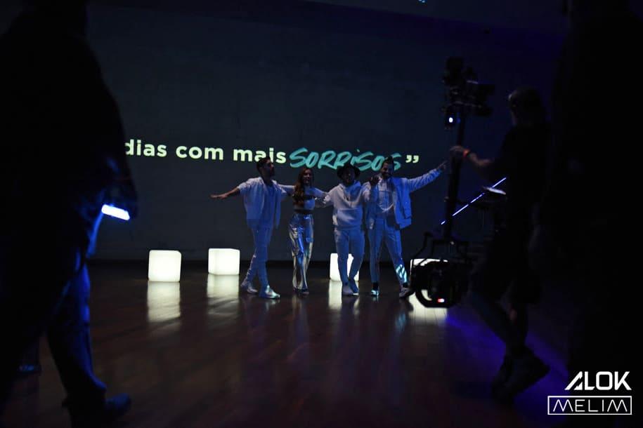 Fotografia do DJ Alok e do grupo Melim, com descrição na legenda.