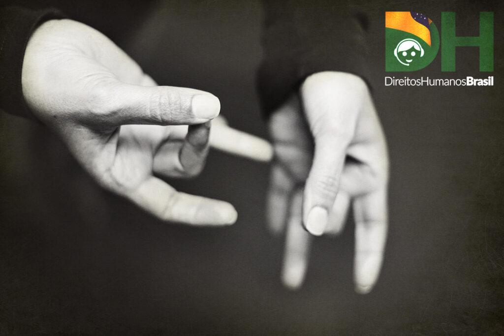 Fotografia de duas mãos sinalizando em Libras e o logo do app dos Direitos Humanos do Brasil.