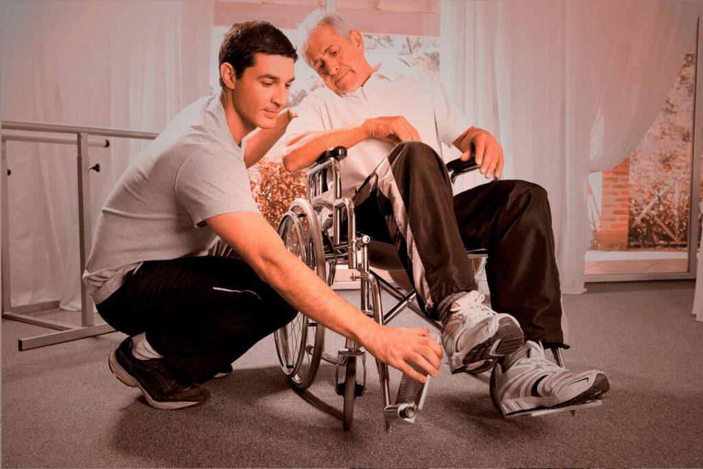 Homem grisalho, em cadeira de rodas, com outro mais jovem, auxiliando a posicionar o pé.