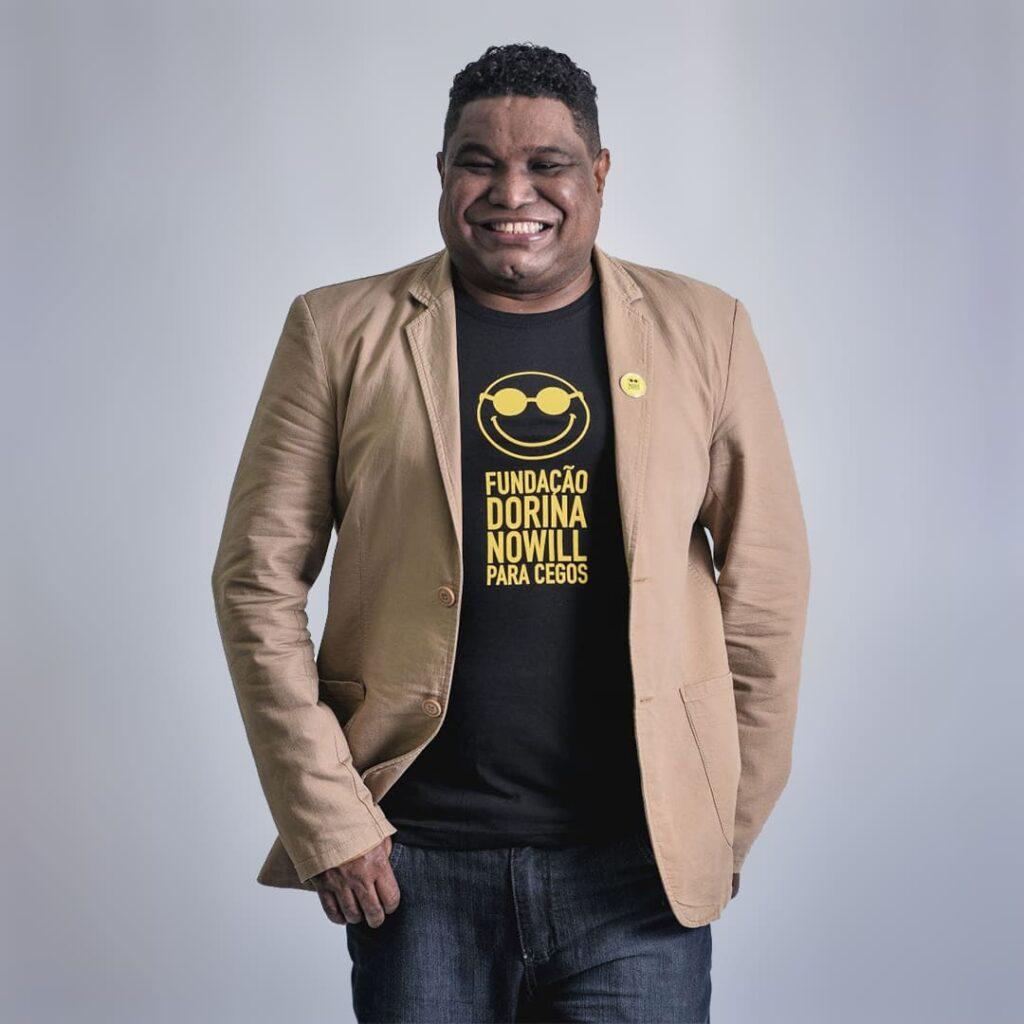 Fotografia do João Maia sorrindo. Ele usa calça jeans, camiseta preta com logo e nome, na cor amarela, da Fundação Dorina Nowill para Cegos e blazer marrom.