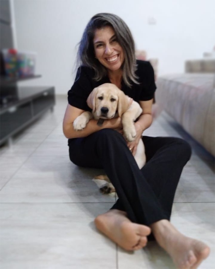 Foto de uma mulher com um cachorro no colo. Descrição na legenda, abaixo.