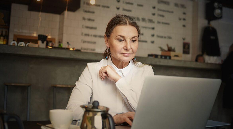 """Mulher idosa, de pele branca e cabelos castanhos, usando um computador, para ilustrar """"5 motivos para contratar um idoso""""."""