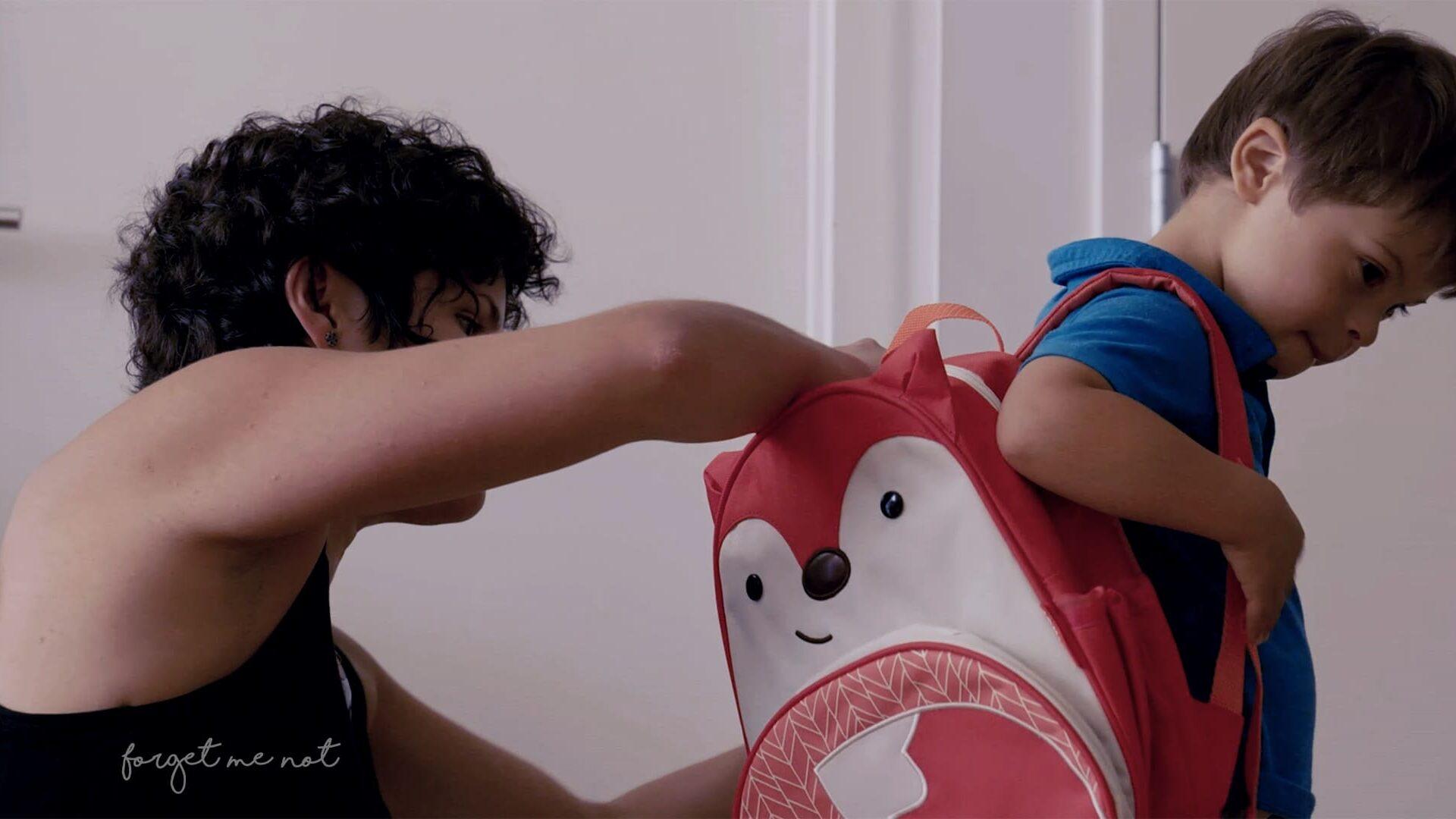 Cena do documentário Um Lugar Para Todo Mundo, com mãe colocando a mochila no filho, que tem síndrome de Down. Descrição na legenda.