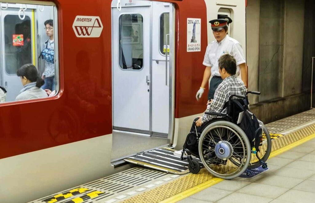 Pessoa em cadeira de rodas acessando o transporte público japonês.